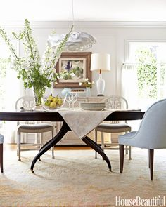 In a Corona del Mar, California, house, Barbara Barry took the edge off the dining room's formality with a Nevo pendant by Arturo Alvarez and a Swedish cabinet. The graceful curves of the vintage and custom chairs echo those of the 1940s table. #diningroom