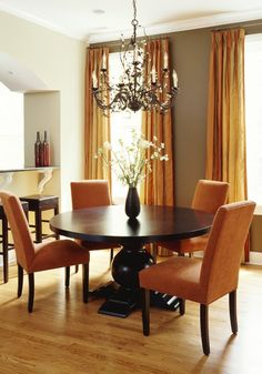 Orange and warm grey dining room.LOVING THE COLOR COMBINATION AND THE ROUND TABLE.