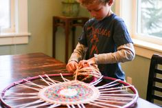 Homemade hula hoop rug:  Hoop for wheel, ripped t-shirts for spokes, finger-knitted yarn for weaving