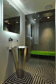 Badfliesen mit 3 D Effekt, freistehendes Becken aus Metall, Spiegel mit LED Beleuchtung, Lautsprecher im Bad, grüne Sitzband in der Duschkabine