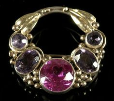 Dorrie Nossiter (attrib.). Arts and Crafts brooch. Silver gilt, set with amethysts and synthetic stone. 3.5 cm diameter. Sold by Dreweatt Neate.