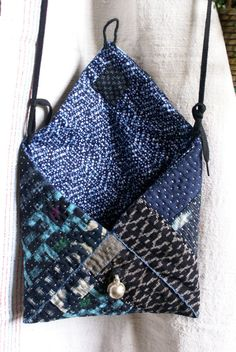 small bag / pouch in vintage japanese kasuri cottons, entirely hand sewn and hand quilted, inspired by sashiko and kantha, Banjara tribal pouches... the Inside lining is in yukata (summer kimono) cotton the inner filling is 100 % cotton i have sewn two small linen loops and a black lace (which is removable) to wear the pouch like a messenger bag it closes with a beautiful antique Rajasthani pearl / pendant, in silver. size : 20 cm x 20 cm lace : approx. 120 cm in case of multiple...