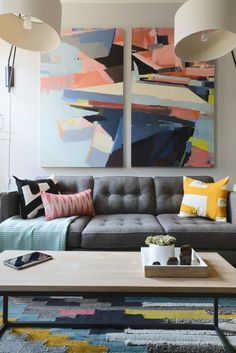 A gray tufted modern sofa with bold colored, patterned abstract art hanging on the wall and a colorful, patterned rug underfoot.