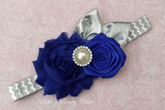 This is a beautiful headband! The blue chiffon rose and a blue satin rose have a white pearl rhinestone in the middle of them. On the top side