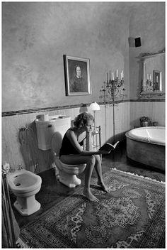 Une pièce comme une autre Jeune femme lisant dans une salle de bain. (Milan – 1997) Ferdinando Scianna / Magnum Photos