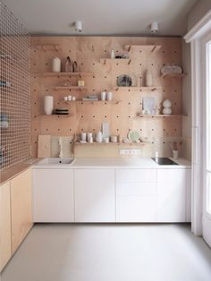 Position Collective created a plywood storage unit that features detachable shelves and pegs that can be reconfigured as needed by the flat's owner, and by visitors.