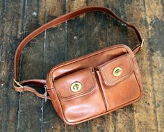 coach waist bag purse // vintage 80s // cognac brown leather // fanny pack // turnlock pockets. $74.00, via Etsy.
