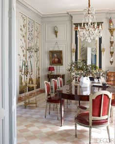 Dining chairs originally made for the socialite Daisy Fellowes, upholstered in an Hermès leather, surround an 18th-century mahogany table in the dining room; the chandelier is by Baguès, and the overmantel mirror is original to the house.   - ELLEDecor.com