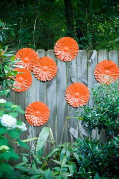 Brightly colored metal art can spruce up a dull wooden fence. #OutdoorDecor #Fences