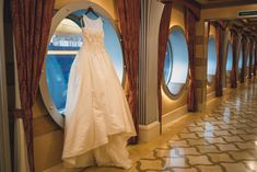A Disney Cruise Line bride's wedding dress hangs in the porthole