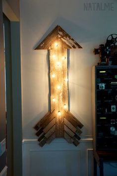 Light up your room with this DIY arrow sign made from reclaimed barn wood and string lights.