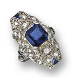 SAPPHIRE AND DIAMOND RING, CIRCA 1920 The shaped panel of arched form and openwork design set in the center with a square emerald-cut sapphire weighing approximately 3.50 carats, completed by numerous small old European-cut and single-cut diamonds weighing approximately 2.50 carats and accented with calibré-cut sapphires, mounted in platinum
