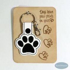 Dog Paw Print Key Fob or Purse Charm: Dogs leave paw prints on your heart! This paw-some key fob is perfect for dog lovers! Made of vinyl and secured with a metal snap, includes a split key ring and optional swivel lobster clasp so you can attach it to your key ring or purse. Arrives gift ready, mounted on a hand-stamped card and wrapped in a 4 x 6 inch clear bag. Card backing design and color may vary from photo samples | SewAmazin #indiemade #doglovers #pawprint