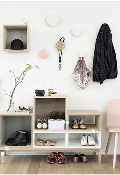 petite entrée moderne aménagée avec un meuble en bois et blanc, une chaise rose et des patères