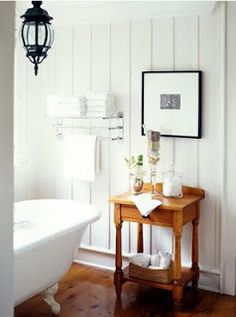 Clawfoot tub, wood floors, and lantern light fixture Basement Bathroom