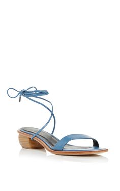 In cornflower blue, these **Tibi** sandals feature a single nappa leather toe strap, a low wooden heel, and an optional ankle tie strap.