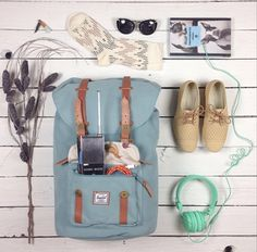 Everyday essentials for the on-the-go woman, featuring the Little America Backpack in Blue.