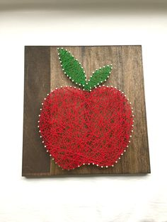"Red Apple String Art - 12"" x 12"" - Nail and White String Art - Handmade - Ready to Ship - Ready to Hang with Hardware - Home Decor - Wall Art. This beautiful string art is made by me in my home. I start by milling the wood, sanding, then staining the wood. Once dried, I pick a pattern, pound the nails in and tie the string to make this amazing artwork. The popular wood is stained in dark walnut and measures approximately 12"" wide by 12"" tall by 2"" deep. This artwork is made in a smoke…"