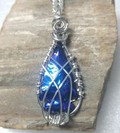 Silver caged titanium aura obsidian arrowhead necklace.