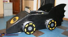 Amy: Boys batman fans - went for the pull along version of the batmobile! Old pram wheels on thick wooden base - made frame nailed together to make basic shape, cardboard. Batman Costume For Boys, Batman Costumes, Boy Costumes, Costume Halloween, Halloween Kids, Halloween Themes, Girl Superhero Party, Batman Car, Cardboard Car