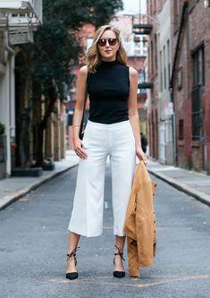 Mulher parada no meio da rua posa para foto de street style usando turtleneck top preto, calça pantalona croppped branca, scarpin amarrações preto, óculos escuros e jaqueta de camurça camelo na mão