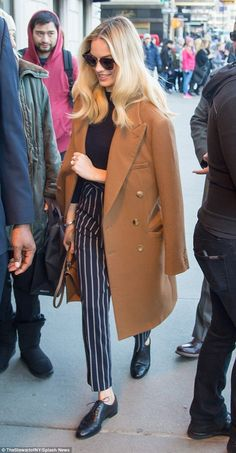 Casual chic: As she sashayed into the venue, the blonde beauty was toting a caramel leathe...