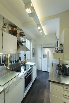 White kitchen on dark floor, very funktional even though the room is very small!  Plan W kitchen in a private home near Hamburg, Germany