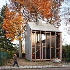 This house has wooden sticks shielding its facades and a tree bursting through its roof: