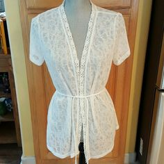 """White lace cover up Like new lace cover up. Light weight.  Has a drawstring you can use at the waist or not. I would wear over a camisole. 100% polyester.  26"""" long. Short sleeve.  Only worn a few times.  Bundle with your favorite jewelry for additional discount.  Nonsmoking home.  All reasonable offers accepted. Romy Tops"""