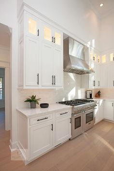 This modern kitchen design is a masterpiece of both style and function. The bright, airy space features high ceilings with a large window that allow ample natural light. White Mouser Centra kitchen cabinets include upper glass front c Refacing Cuisine, Refacing Kitchen Cabinets, White Kitchen Cabinets, Kitchen Cabinets With Glass Doors On Top, Teal Cabinets, Kitchen Cabinets To Ceiling, White Granite Kitchen, Cabinet Refacing, Modern Cabinets