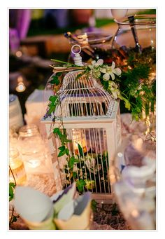 White wooden bird cage with flowers for centerpiece.