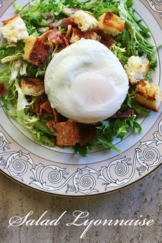 Poached Egg and Bacon Salad – Salad Lyonnaise ~ Traditional French salad Lyonnaise with frisee lettuce, bacon, croutons, a poached egg, and a Dijon vinaigrette. ~ SimplyRecipes.com