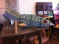 Made from recycled wood. Two-toned, blue and green fish with white stripes.  This one swam home to Hyannis.
