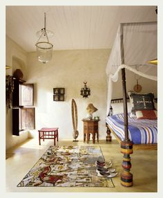 Love this gauze four-poster hanging rolled up so cute... the Indian bedrame, the tropical style bedspread, lovely flat weave rug and subtle feel of room. Love the light fixture and also the paneled ceiling.
