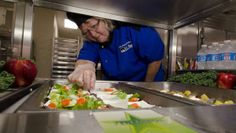 A cafeteria employee serves a school's healthy lunch, reflecting a change in the quality of school cafeteria food.