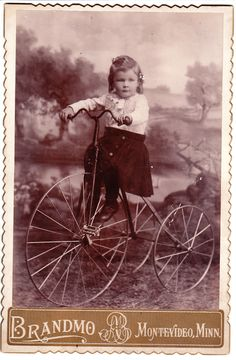 LITTLE GIRL RIDING A GIANT TRICYCLE IN MONTEVIDEO, MINNESOTA