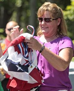 Laurie Hayes collects the bunting that had draped a sign naming the Broad Street Bridge in Bridgewater for her son, Marine Lance Cpl. Kevin T. Preach, who was killed in Afghanistan in 2009. A dedication ceremony was held Sunday. Emily J. Reynolds/The Enterprise