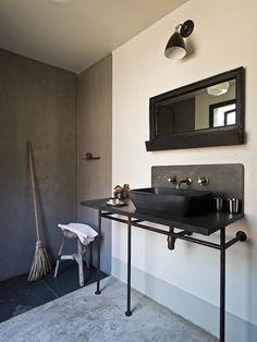 Industrial style bathroom with gray tadelakt shower surround over dark gray tadelakt tiled floors topped with a rustic tripod stool.