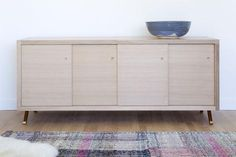 A storage unit with four sliding doors and plenty of shelving space. The Atwatercredenza sits on polished metal legs, which are available in copper, brass, and