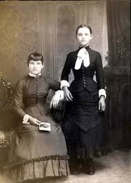 victorian death photo - the girl standing is deceased (you can tell by the posing of her hand)