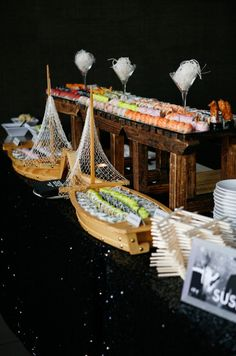 A sushi station displaying confections in wooden ships celebrates a nautical themed wedding.