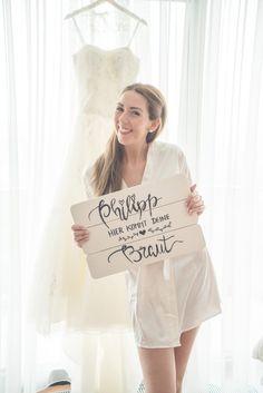 """#Braut Jennifer mit Schild für die #Hochzeit für ihr Kind mit der Aufschrift: Philipp hier kommt deine Braut. Alternativ könnte man auch """"Papa hier kommt deine Braut"""" drauf schreiben. Foto: Viktor Schwenk Photographie"""