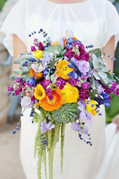 Lavender, Blue Delphinium, Fuchsia Stock, Succulents, Yellow and Orange Ranunculus, Lavender Sweet Peas, Yellow Freesia, and Green Hanging Amaranthus