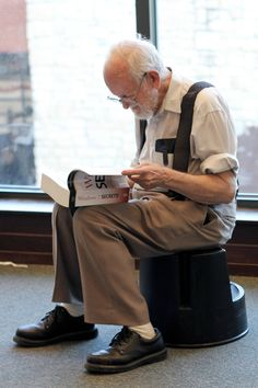 A cute old man reading up on windows 7 in a bookstore.