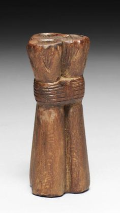 An Egyptian wood cosmetic vessel  New Kingdom, 18th Dynasty, circa 1550-1295 B.C. In the form of three lotus flowers with the stems bound together, each flower drilled through the centre for a kohl stylus, 3¼in (8.3cm) high