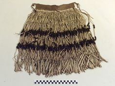 Hupa woman's ceremonial skirt's apron. About 1880. Materials include deerhide, bear grass, pine nuts, hide thong.  Collected by Alexander A. Brizard (1839-1904, a shopkeeper in Arcata, California, who sold Indian baskets and other items); presumably purchased by George Heye in 1904. LBD