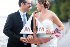 bride and groom holding a custom wooden sailboat with their initials and American flag, crafted by the bride's brother   nautical wedding