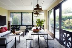 When it came to the decor, the homeowners and designer were in sync, favoring clean-lined furniture—like the ebonized-oak dining table and 1950s leather sling chairs—but avoiding extraneous flourishes such as window treatments. The carefully chosen accessories include a Burmese bronze chain suspended from a living room wall and an enormous antique Spanish olive jar in the master bedroom. A pair of Art Deco–era industrial lights hangs above a custom-made table and benches in the screened ...