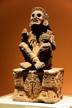 Xochipilli - Aztec God of Art. The god of art, games, beauty, dance, flowers, maize, and song in Aztec mythology, seated cross-legged on his throne. The name means Prince of Flowers. Origin: Tlalmanalko, Mexico. Location of the statue: Museo Nacional de Antropologia, Mexico City.