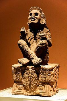 Xochipilli - deus asteca da arte. O deus da arte, jogos, beleza, dança, flores, milho, e música na mitologia asteca, sentado de pernas cruzadas em seu trono. O nome significa Príncipe das Flores. Origem: Tlalmanalko, no México. Localização da estátua: Museo Nacional de Antropologia, Cidade do México.